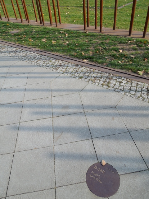 "The plaque here located on what was once the West Berlin side of the Berlin Wall reads, ""Escape, One Woman"""